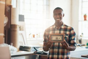 Portrait of a proud young African entrepreneur smiling at the camera and holding a framed dollar bill, which is the first money his business earned, and supports investing in small business growth